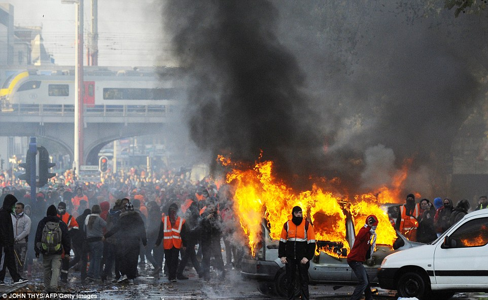 Hundreds of protesters mill around as vehicles burn after violence broke out at the end of a mass march