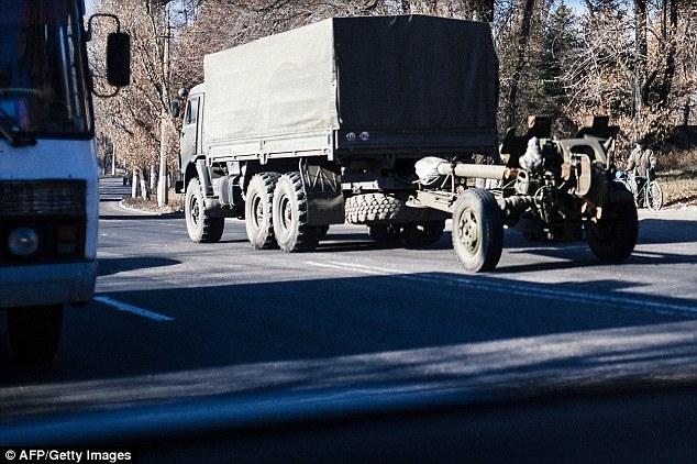 Camiones sin placas remolcar una pieza de artillería de 122 mm obús través Makiivka en Ucrania