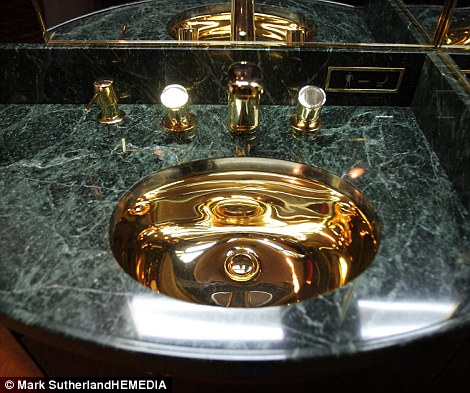 Fit for royalty: The bathroom has marble sinks with gold faucet and a toilet hidden beneath a leather chair