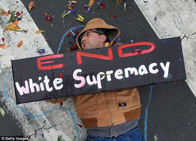 Making a statement: A demonstrator holds a sign that reads, End White Supremacy, as he lays on the ground during a protest over the death of Michael Brown on November 16, 2014 in St. Louis, Missouri