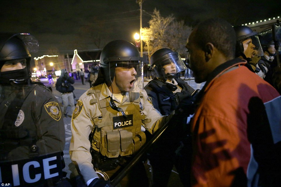 Stand-off: Witnesses on the ground in Ferguson say police have been shooting bean bag rounds and stun grenades into the crowd along with tear gas. Above, police officers confront protesters following the unpopular decision not to indict Officer Wilson was announced Monday night