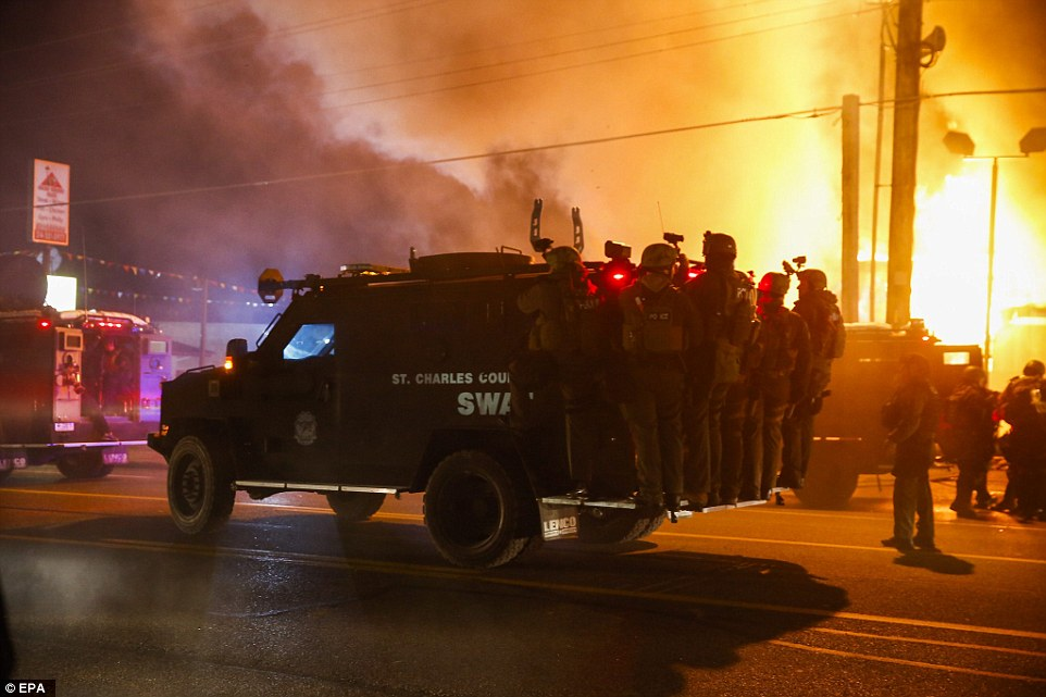 Chaos: Police ride on a vehicle past a burning building that was set ablaze by protestors in Ferguson