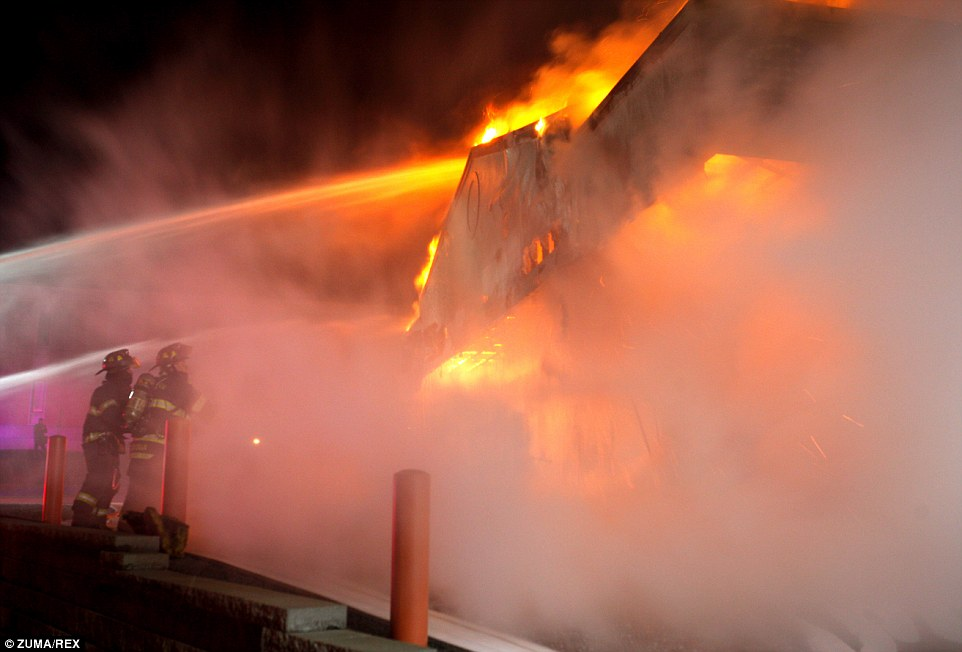 Night of extremes: Firefighters work to extinguish a blaze, set by rioters, at a Little Caesar's restaurant in Ferguson