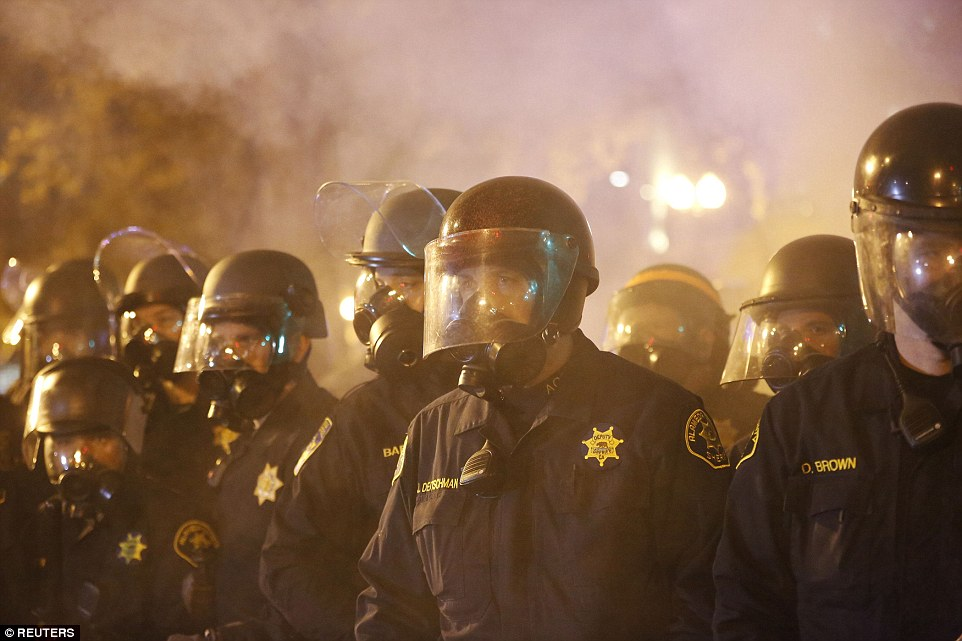 Police officers in gas masks in Oakland, California, form a line during a demonstration over the shooting of Michael Brown