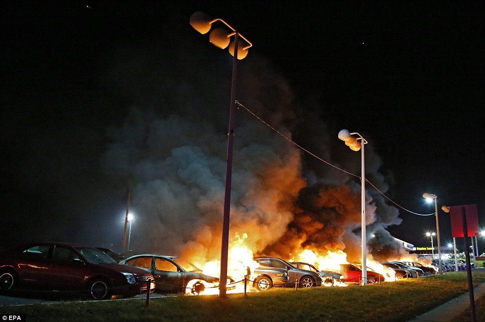 Burning: Cars parked outside one row of shops on West Florissant were targeted in the destruction spree