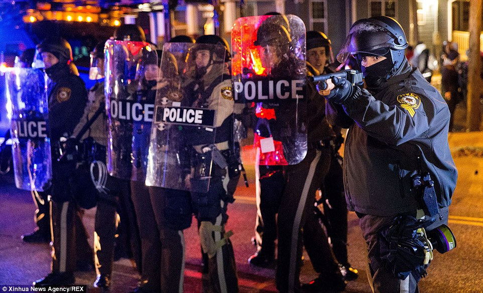 Confrontation: A police officer aims his non-lethal shotgun at protestors in Ferguson