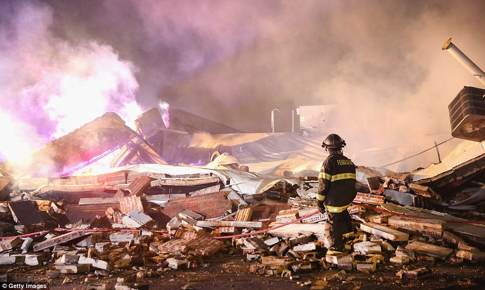 Heart-breaking: Parts of Ferguson were left looking like a war zone after rioters set buildings ablaze and looted shops