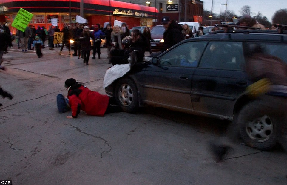 Shocking: The motorist, who has not been identified, was captured on video speeding toward the group in a dark-colored Subaru Outback. He plowed through demonstrators, before smashing into a woman and carrying her along the road under his left-front wheel (pictured)
