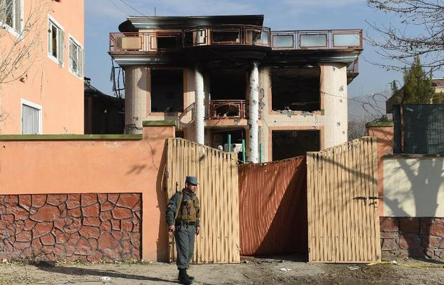 An Afghan policeman keeps watch at the gate of a foreign compound following a Taliban attack in Kabul on November 30, 2014