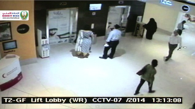 The burqa-clad suspect lifts a free newspaper before heading into the toilets of the mall