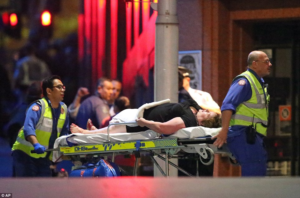 An injured hostage is carried away on a stretcher by paramedics after police stormed the Lindt Chocolat cafe in central Sydney where around 20 people were being held by a gunman during a 17-hour siege. One hostage and the gunman were reportedly killed in the firefight