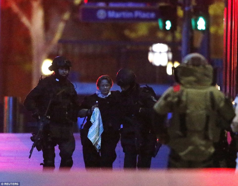 Petrified: Two heavily armed police officers assist a hostage away from Lindt Cafe in Martin Place in central Sydney