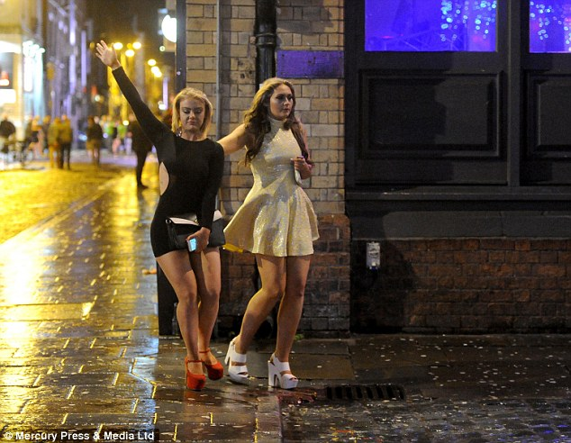 Two young women, wearing short dresses and platform shoes, enjoy a night out in Liverpool on Mad Friday