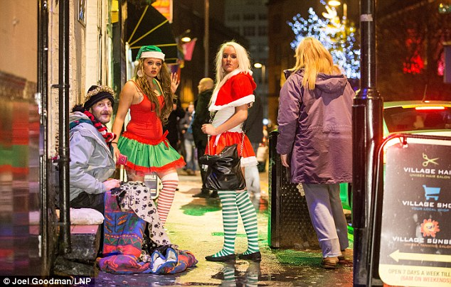 Two women dressed in festive costumes with striped stockings outside Napoleons in Manchester