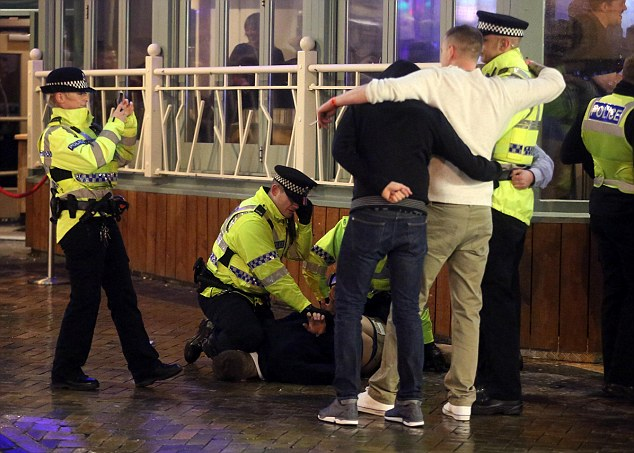 In Blackpool, a policewoman takes a photograph of two revellers as her colleague struggles to arrest a man on the pavement