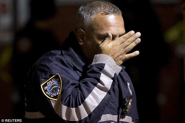 Emotional:A police officer wipes tears away from his face as he walks away from the scene of a shooting