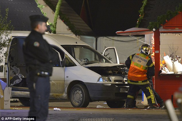 Firefighters inspect the engine of a white van driven into crowds at a Christmas market in Nantes on Monday