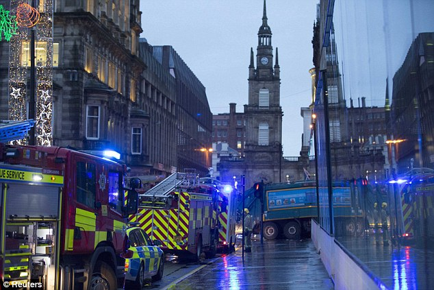 The lorry can be seen sticking out from the hotel wall as emergency workers survey the crash site
