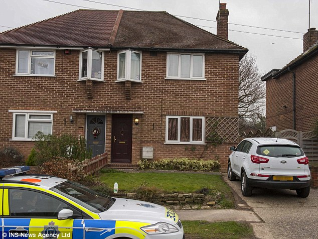 Police outside the West Sussex home where the parents of two young children were found dead yesterday