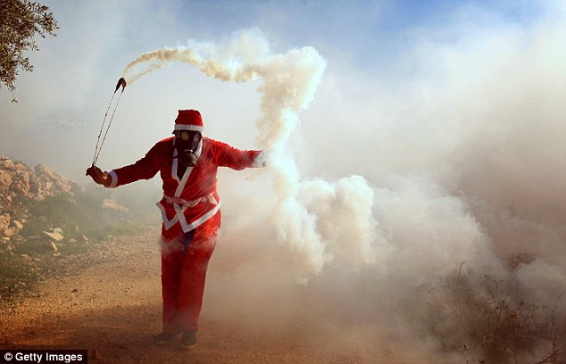 The Palestinian man in the Father Christmas costume was pictured throwing a tear gas capsule