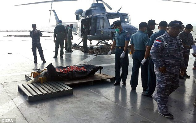 Analysts agreed the aircraft had been buffeted by 'freakishly extreme' weather making it impossible to save any of the 162 people on board (pictured, rescue workers recover a body today bringing the total to nine)