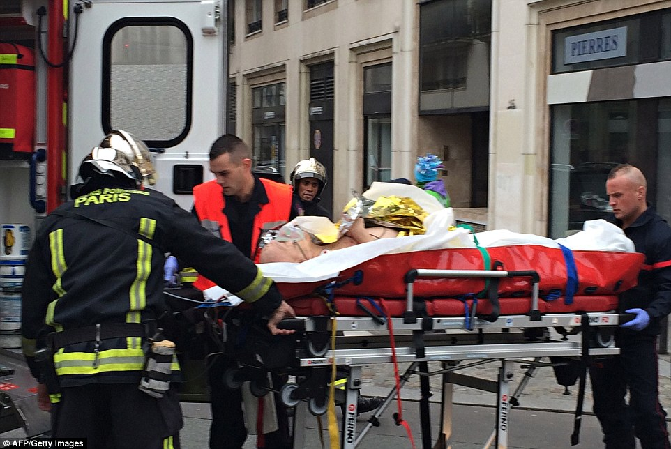 Critical: Firefighters carry an injured man on a stretcher in front of the offices of French satirical paper Charlie Hebdo after the shooting