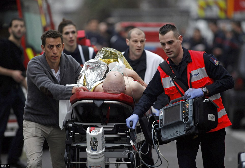 Life-threatening: An injured person is evacuated outside the French satirical newspaper Charlie Hebdo's office