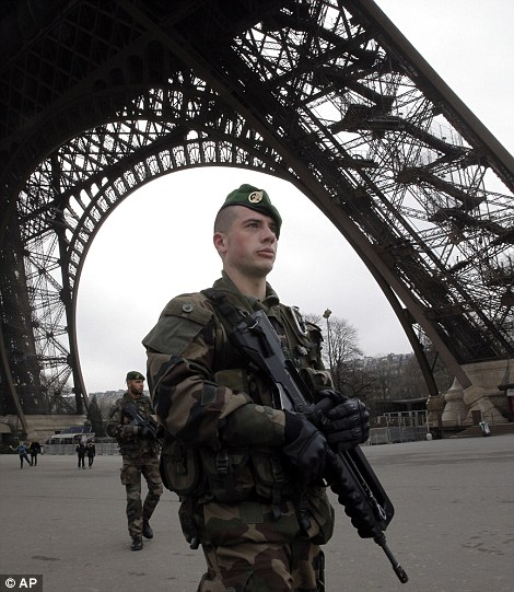 French soldiers patrol at the Eiffel Tower after a shooting at a French satirical newspaper, in Paris, France, Wednesday, Jan. 7