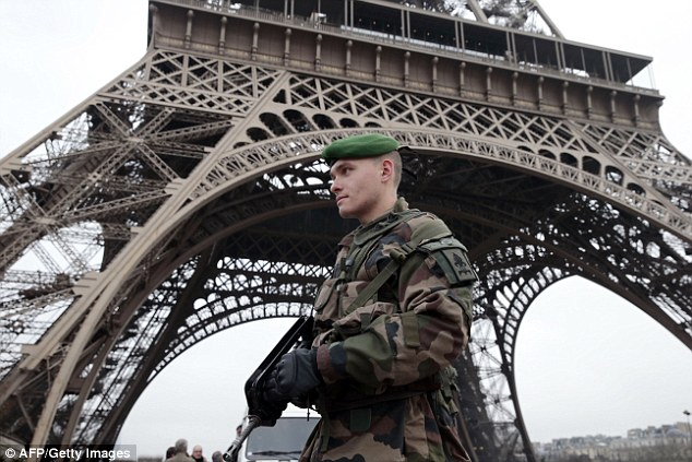 Lockdown: The streets of Paris are being patrolled by soldiers dressed in combat fatigues and carrying Famas assault rifles this afternoon after a terror attack killed 12 people earlier in the day