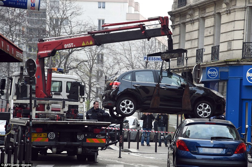 A truck tows the car apprently used by armed gunmen who stormed the Paris offices of satirical newspaper Charlie Hebdo, killing 12 people