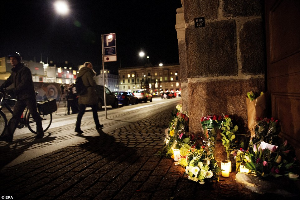 People walk past flowers that have been laid in tribute to victims of the attack in front of the French Embassy in Copenhagen, Denmark