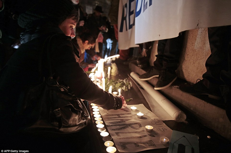 A woman lights a candle during a gathering at the Place de la Republique, another example of the peaceful protests being held tonight