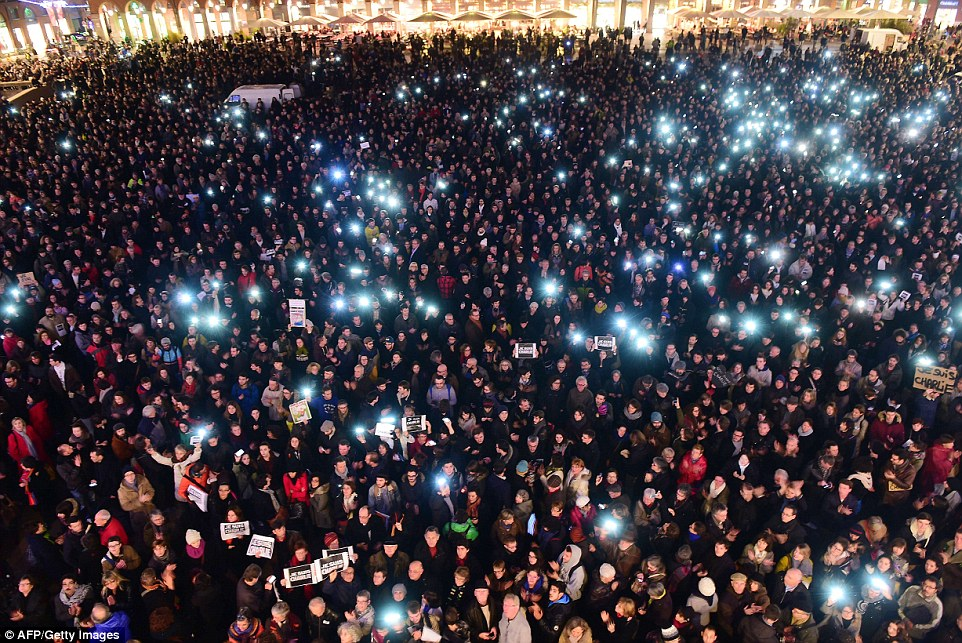 Unity: Protesters hold up their phones at a vigil held in Toulouse. Francoise Hollande has declared tomorrow a day of national mourning