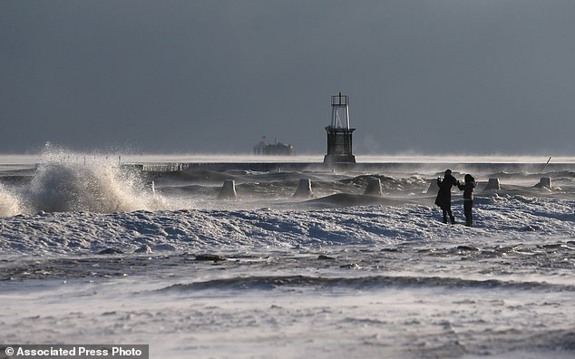 A pair of onlookers take pictures as waves crash at North Avenue Beach along the Lake Michigan shore on Wednesday, January 7, 2015