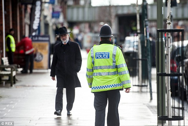 A Metropolitan police officer patrols an area of North London with a large Jewish population yesterday