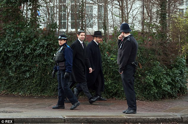 A police officer speaks to a pair of men in an area of North London which has a large Jewish population