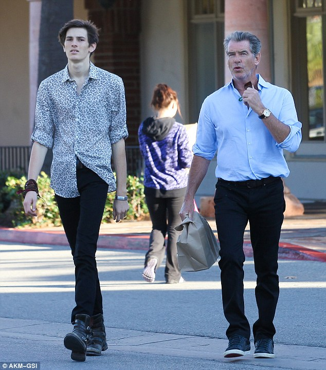 "Longer than daddy's long legs: Model Dylan, who turned 18 on Tuesday, towered over his 6'1"" father"