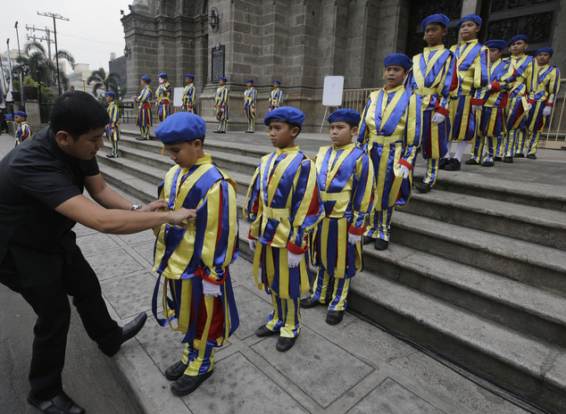 A Catholic priest adjusts the uniform of boys who are dressed as Vatican Swiss guards during a rehearsal for the visit of Pope Francis outside the Manila Cat...