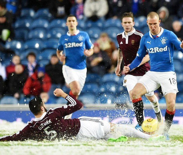Striker Kenny Miller Right Tries To Avoid A Tackle From Hearts Alim Ozturk