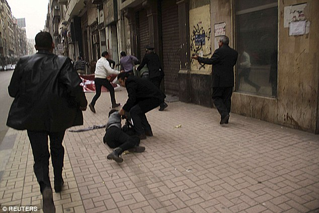 Al-Sabbagh can be seen, right, hitting the ground as a fellow protester comes to her aide during the clashes