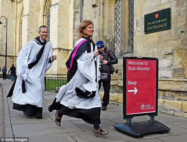 Excitement: Two members of the clergy run into York Minster ahead of the service
