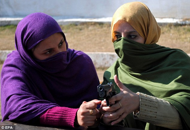 Two teachers watch on as they are taught how to operate a handgun, training which will allow them to 'engage' terrorists should their school come under attack