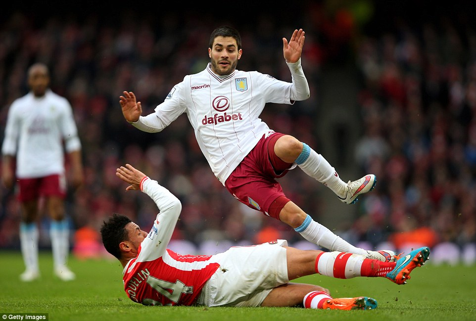 Arsenal's French midfielder Francis Coquelin sends Aston Villa's new signing Carles Gil flying with a slide-tackle