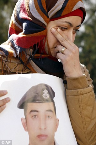 Anwar al-Tarawneh, the wife of Jordanian pilot, Lt. Muath al-Kaseasbeh, who is held by Islamic State group militants, holds a poster of him as she weeps during a protest in Amman, Jordan, Tuesday, Feb. 3, 2015. Al-Kaseasbeh was seized after his F-16 jet crashed near the Islamic State group's de facto capital, Raqqa, Syria, in December last year. (AP Photo/Raad Adayleh)