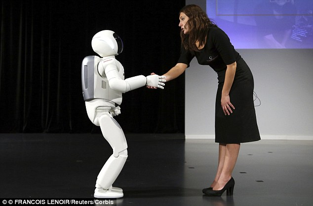 The issues raise the question of whether AI can have a soul. Pictured is Honda's Asimo humanoid robot shaking hands during a presentation in Zaventem near Brussels