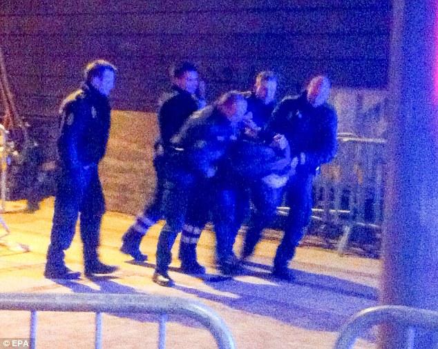 """Detención: La policía arresta a un hombre no identificado poco después del tiroteo sinagoga.  Se cree que el hombre detenido no es el sospechoso """"pistolero solitario 'que mató a un hombre e hirió a dos policías en el segundo ataque del día"""