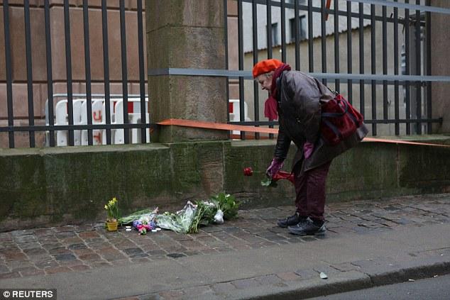 Una mujer pone una sola rosa roja frente a un edificio cerca de la Gran Sinagoga tras el tiroteo de anoche.  El líder de Israel condenó el ataque contra el judaísmo, el fomento de una inmigración masiva desde Europa