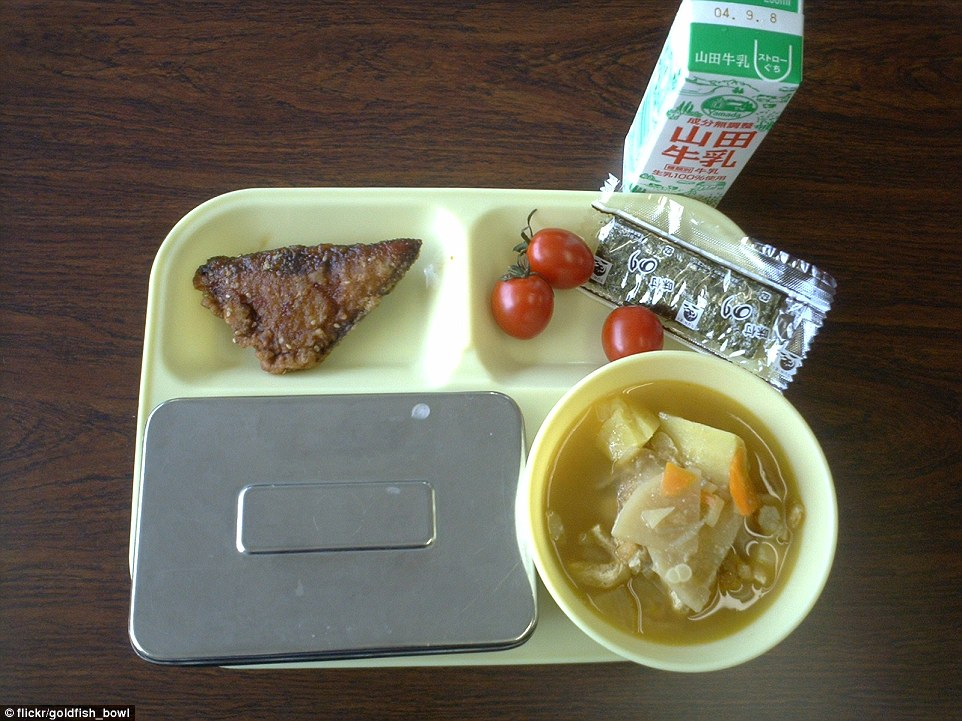 In Japan, school children tuck into fried fish, dried seaweed, tomatoes, miso soup with potatoes, rice (in the metal container), and milk