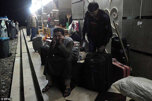 Anxious: The Egyptians who fled their adopted home in Libya face a nervous wait before passing through the border village Sallum