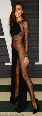 Model Irina Shayk turns heads at the Vanity Fair Oscars party in an Atelier Versace gown boasted a cutaway feature down one entire side, with the missing material replaced by a sheer mesh catsuit
